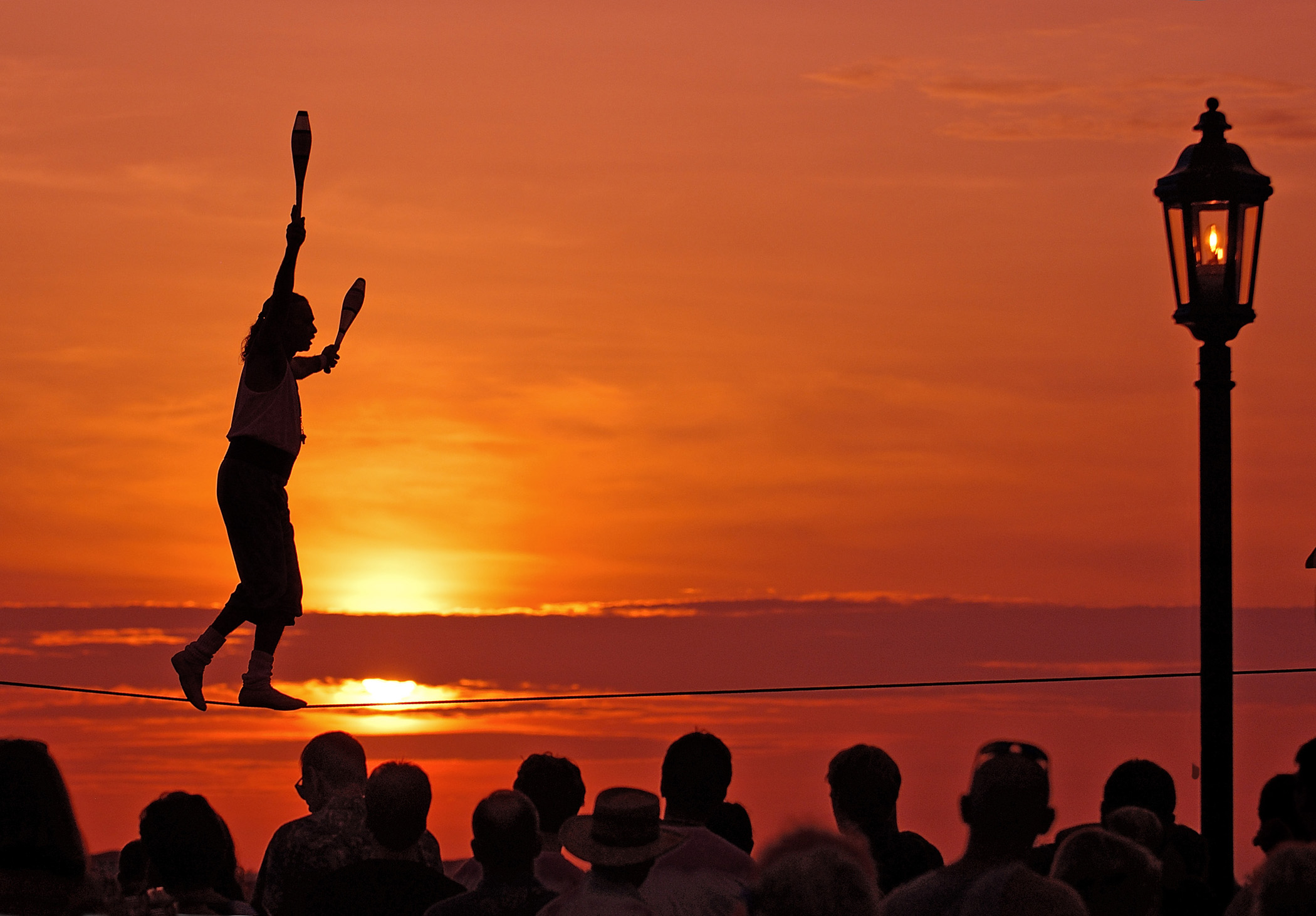 Busker Will Soto walks a tightrope at the sunset celebration in Key West, Fla. The sunset celebration at Mallory Square is a daily ritual for visitors to this subtropical island at the bottom of the Florida Keys island chain. Photo by Bob Krist/Florida Keys News Bureau